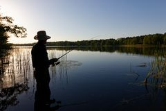 Fisherman. Silhouette of fisherman standing in the lake and catching the fish at sunny day stock photo