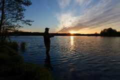 Fisherman. Silhouette of fisherman standing in the lake and catching the fish during sunrise Royalty Free Stock Images