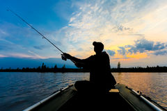 Fisherman silhouette with fishing rod  in the inflatable boat at sunrise and throws a  lure for catching fish Stock Photography