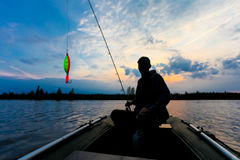 Fisherman silhouette with fishing rod is sitting in the inflatable boat and bright lure on the foreground at sunrise Royalty Free Stock Images