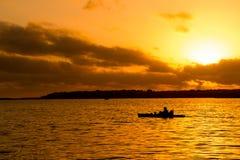 Fisherman silhouette in kayak and lake sunset. Fisherman silhouette in kayak and orange lake sunset Royalty Free Stock Photos