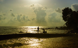 Fisherman silhouette in last rays of sunlight. Stock Photos