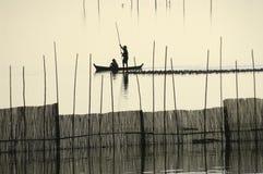 A fisherman silhouette near U Bein's Bridge. Royalty Free Stock Image