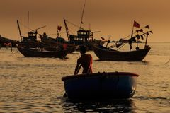 Fisherman Silhouette Rows in Round Boat with Paddle at Sunset Royalty Free Stock Images