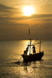 Fisherman silhouette in sea at sunrise Stock Images