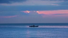 Fisherman silhouette in small fishing boat on the ocean at nightfall with orange sunset. Royalty Free Stock Photos
