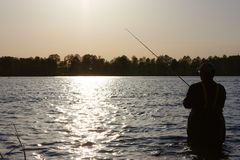 Fisherman. Silhouette of fisherman standing in the lake and catching the fish on sunny day Royalty Free Stock Photos