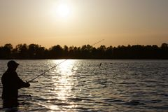 Fisherman. Silhouette of fisherman standing in the lake and catching the fish during sunny day Royalty Free Stock Image