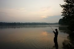 Fisherman. Silhouette of fisherman standing in a lake and catching the fish during sunrise Stock Photos