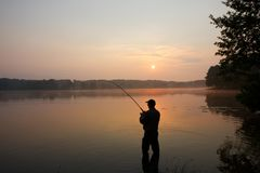 Fisherman. Silhouette of fisherman standing in a lake and catching the fish during sunrise Royalty Free Stock Image