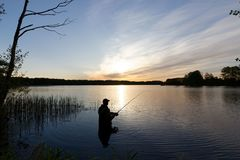Fisherman. Silhouette of fisherman standing in the lake and catching the fish during sunrise Stock Photos