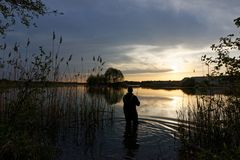 Fisherman. Silhouette of fisherman standing in the lake and catching the fish during sunset Stock Image