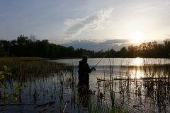 Fisherman. Silhouette of fisherman standing in the lake and catching the fish during sunset Stock Photo