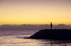 Fisherman silhouette at sunrise. A fisherman at sunrise on a beach in Sousse, Tunisia Stock Photography
