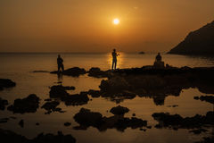 Fisherman silhouette at sunrise. Three fishermen fishing in the ocean at sunset Stock Image