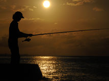 Fisherman silhouette at sunset. Portrait of fisherman silhouette against sunset sky background Stock Photography