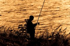 Fisherman Silhouette on sunset. Stock Photography