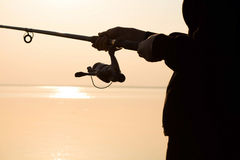 Fisherman silhouette at sunset with a fishing rod Royalty Free Stock Photography