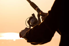 Fisherman silhouette at sunset with a fishing rod Stock Photo