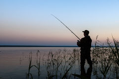 Fisherman silhouette at sunset. On the lake while fishing Stock Images