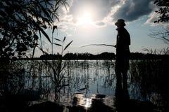 Fisherman silhouette. Man fishing on the lake on vacation