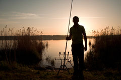 Fisherman silhouette at sunset near the lake Stock Images