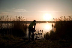 Fisherman silhouette at sunset near the lake Stock Photography
