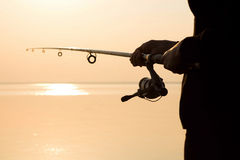Fisherman silhouette at sunset near the sea with a fishing rod Royalty Free Stock Image