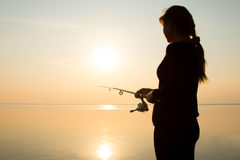Fisherman silhouette at sunset near the sea Stock Image
