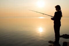 Fisherman silhouette at sunset near the sea Royalty Free Stock Photography
