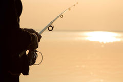 Fisherman silhouette at sunset near the sea with a fishing rod Stock Photos