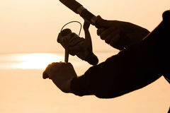 Fisherman silhouette at sunset near the sea with a fishing rod Royalty Free Stock Photos