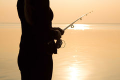 Fisherman silhouette at sunset near the sea with a fishing rod Stock Image