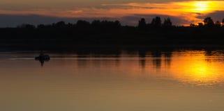 Fisherman silhouette at sunset. Stock Photo