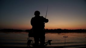 Fisherman silhouette throwing fishing rod in river and sitting down on chair. On background evening sunset. Beautiful evening sunset during fishing on river stock footage