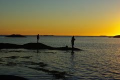 Fisherman silhouettes against sunset. Fisherman silhouettes with angles against sunset light Royalty Free Stock Photography