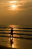 Fisherman Silhouettte in Beach Sunrise. Fisherman Silhouetted in a Beach Sunrise on the Eastern Coast of Florida Royalty Free Stock Photos