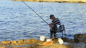 Paphos, Cyprus - September 17, 2017- Fisherman with fishing rod at stone shore. Fisherman sits on the chair near the river with fishing rod. Elderly man cathes stock footage