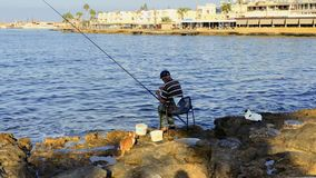 Paphos, Cyprus - September 17, 2017 - Fisherman with fishing rod at shore. Fisherman sits on the chair near the river with fishing rod. Elderly man cathes fishes stock footage