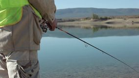 Fisherman Sits With A Fishing Rod In The Water Reservoir And Hooking Fish. stock video footage