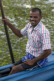 A fisherman sits in his pontoon boat prior to taking a group of tourists for a trip on Pottuvil Lagoon. A fisherman sits in his pontoon boat prior to taking a Royalty Free Stock Photo
