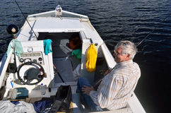 Fisherman sitting in a boat with spinning Royalty Free Stock Photos