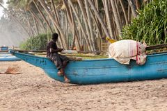 A fisherman sitting on a boat. Sri Lanka. An old fishing boat on a sandy beach. Green tropical trees, palm trees Stock Photos
