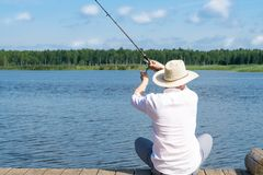Fisherman sitting on the bridge catches fish, active recreation stock photography