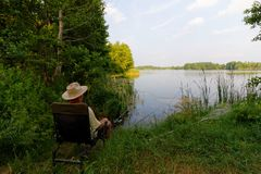 Fisherman. Sitting on the chair and fishing on the shore of a lake during sunny day Royalty Free Stock Photo