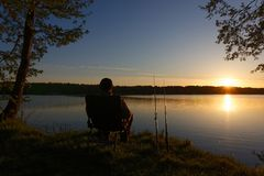 Fisherman. Sitting on the chair and fishing on the shore of lake during sunrise Royalty Free Stock Photography
