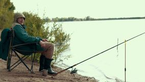 Fisherman sitting on chair by river nearly fishing rod waiting for bite. Summer leisure fishing on river stock footage