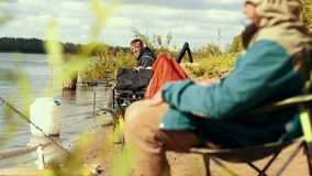 Fisherman sitting on chair by river nearly fishing rod waiting for bite. Summer leisure fishing on river in sunny day stock footage