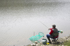 Fisherman Sitting In The Chair On The Riverside Reeling String And Throwing Rod Into The River royalty free stock photo