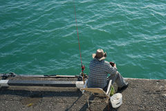 Fisherman sitting on the pier at the blue calm sea. And catching fish Stock Photography